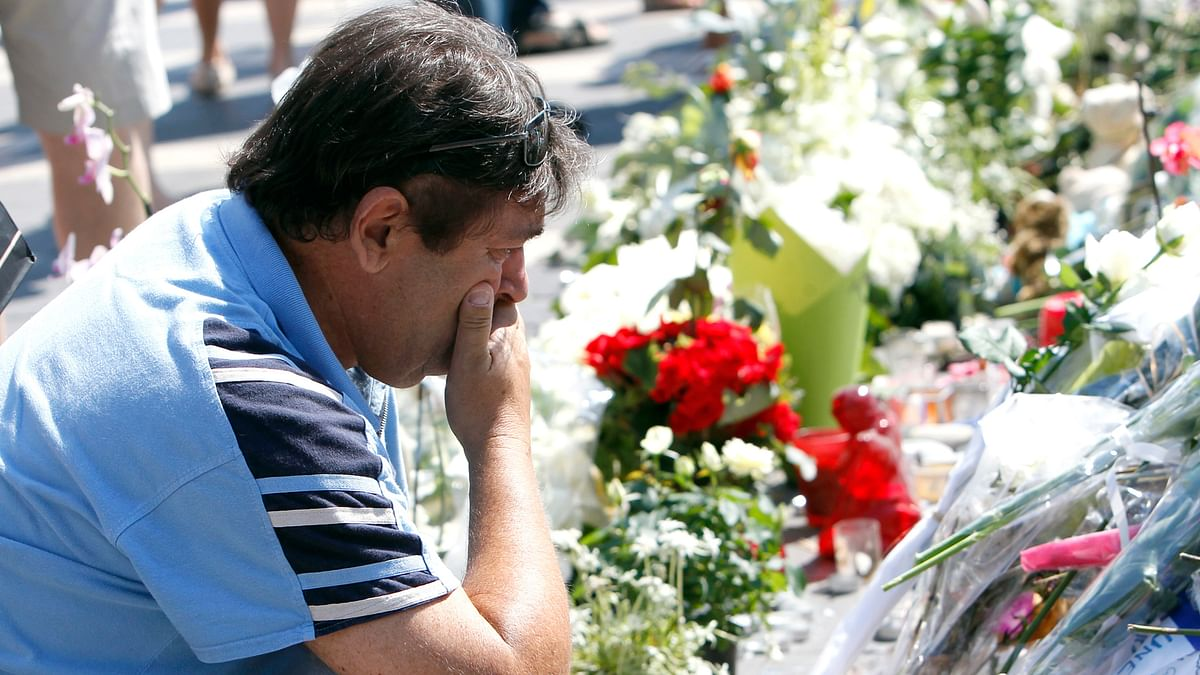 A man mourns as he looks at the flowers placed at a new memorial in a gazebo in a seaside park of the Promenade des Anglais in Nice. (Photo: AP)
