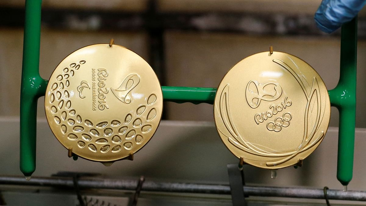 A worker takes out gold-plated Olympic and Paralympic medals. (Photo: Reuters)