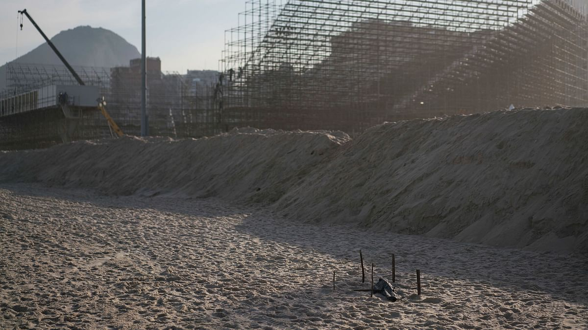 A human dismembered foot is covered with a black plastic after it was found on the beach in front of the Olympic beach volleyball venue still under construction at Copacabana in Rio de Janeiro. (Photo: AP)<a></a>