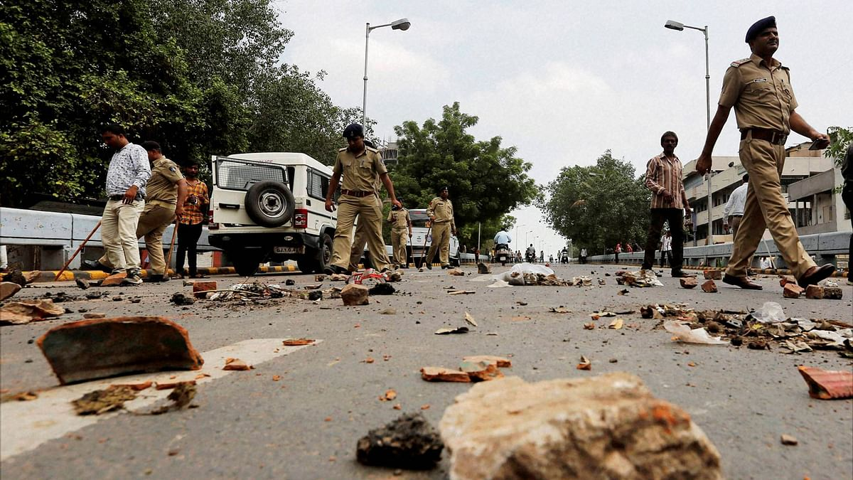 Policemen remove stones put by members of Dalit community to block traffic during their protests in Ahmedabad on Wednesday. (Photo: PTI)