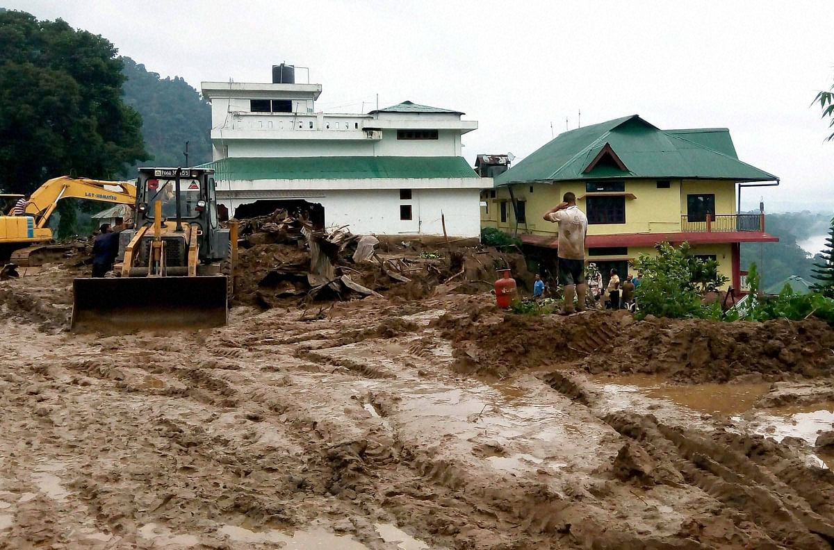 Workers busy in cleaning the debris of massive landslide that buried several houses at Bhalukpong in Arunachal Pradesh on Friday. (Photo: PTI)