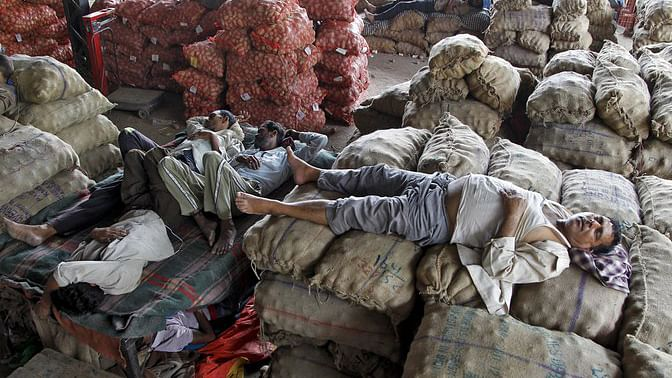 Vendors take a nap on stacked sacks of vegetables at a wholesale market on a hot summer day in Chandigarh, India, 29 May 2015. (Photo: Reuters)