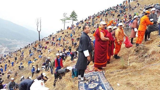 Bhutanese people planting saplings on a hillside, in Thimpu, Bhutan. (Photo: AP)