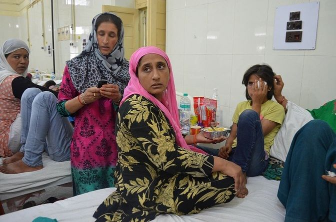"""""""They deliberately fired at our houses,"""" says Shameema, Tamanna's mother, while trying to feed her daughter in Shri Maharaja Hari Singh Hospital. (Photo: Pradeepika Saraswat)"""