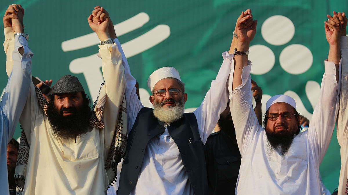 Hafiz Saeed, chief of Jamaat-ud-Dawa joins hands with Sirajul Haq, center, and the leader of Hizbul Mujahideen Syed Salahuddin, left, during the anti-Indian rally in Islamabad. (Photo: AP)