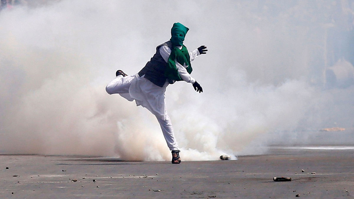 A demonstrator throws stones amid tear gas smoke fired by Indian police during a protest against what protesters say is the house arrest of Kashmiri separatist leaders, after Eid al-Fitr prayers in Srinagar. (Photo: Reuters)