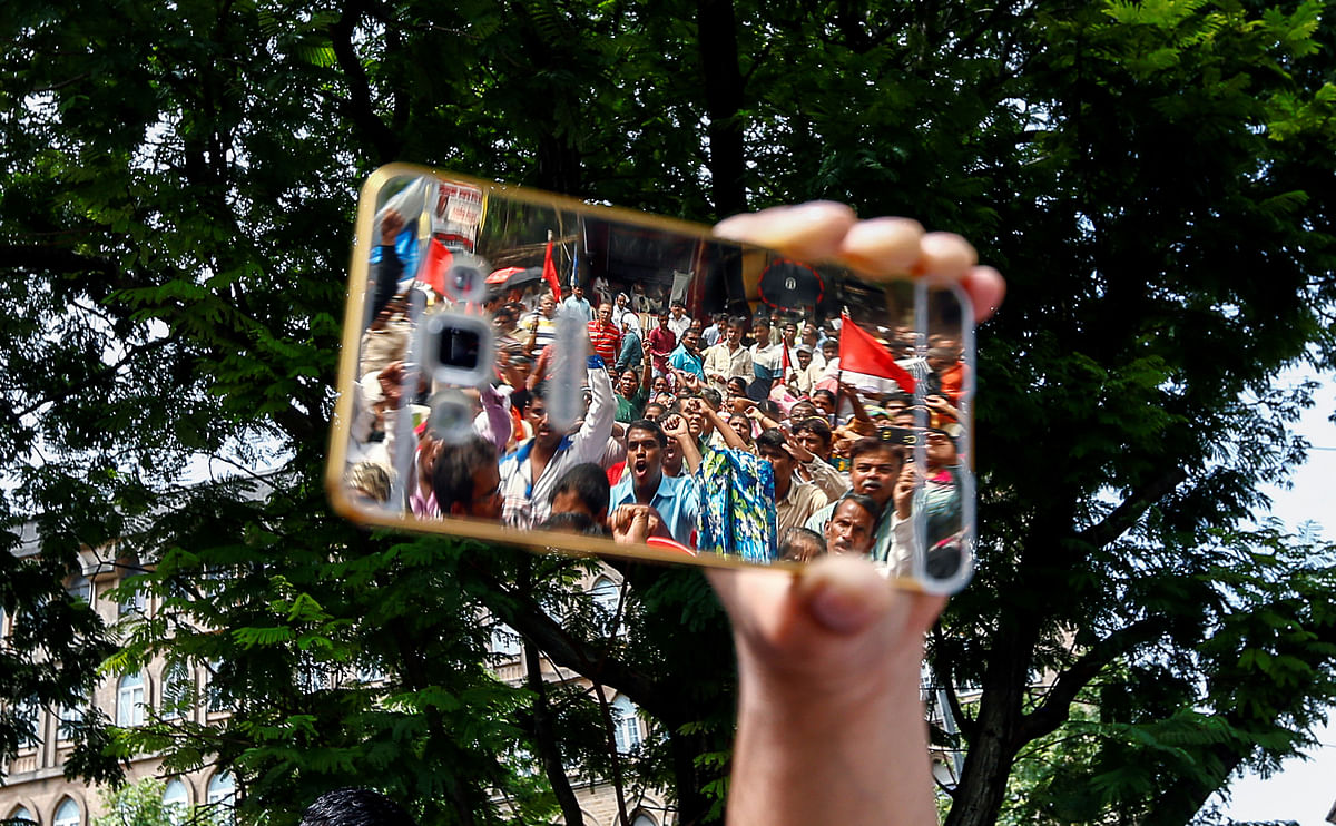 People  reflected on a phone as they attend a protest against what  attacks on the  dalit community in Mumbai, 12 August  2016. (Photo: Reuters)