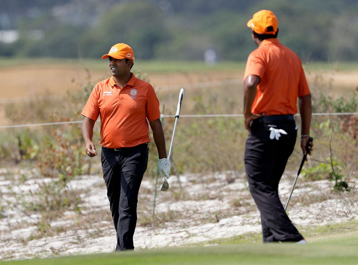 Anirban Lahiri, of India, left, looks at his shot from the rough on the fifth green watched by SSP Chawrasia, of India, during a practice round for the men's golf event. (Photo: AP)