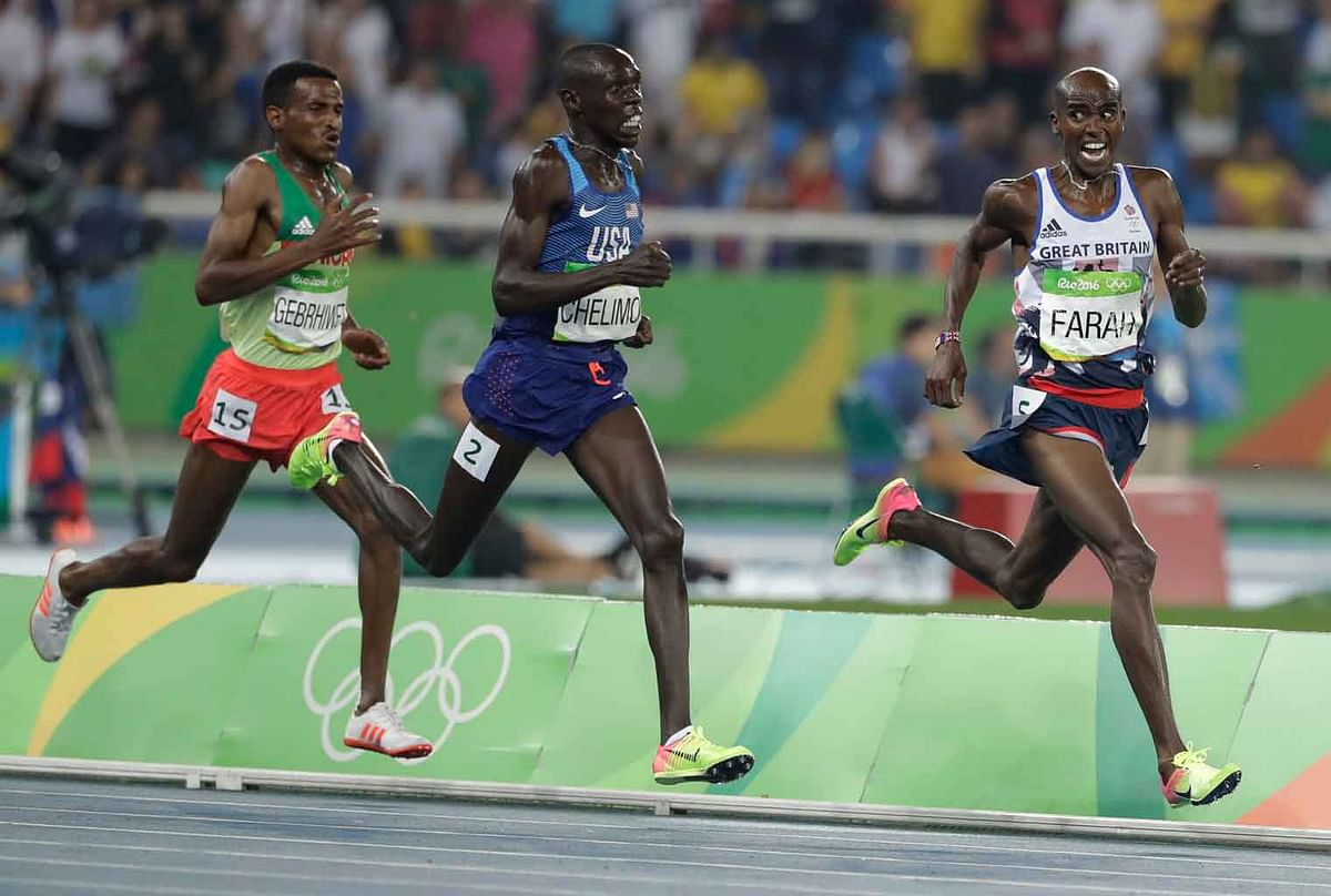 Britain's Mo Farah leads United States' Paul Kipkemoi Chelimo, center, and Ethiopia's Hagos Gebrhiwet to win the men's 5000-meter final during athletics competitions at the Summer Olympics inside Olympic stadium in Rio de Janeiro, Brazi. (Photo: AP)