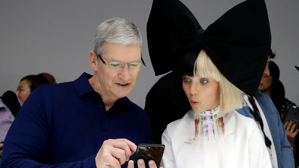Apple CEO Tim Cook shows an iPhone 7 to performer Maddie Ziegler during an event to announce new products, Wednesday, in San Francisco. (Photo: AP Photo)<a></a>