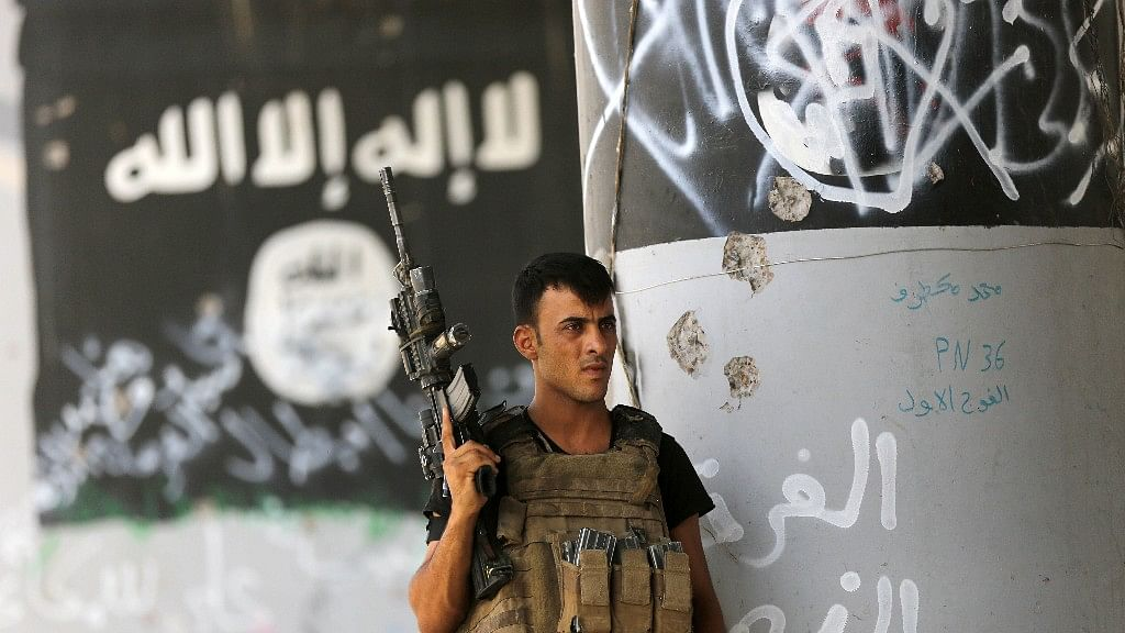 In this file photo from 27 June 2016, a member of Iraqi counterterrorism forces stands guard near Islamic State group militant graffiti in Fallujah, Iraq. (Photo: AP)