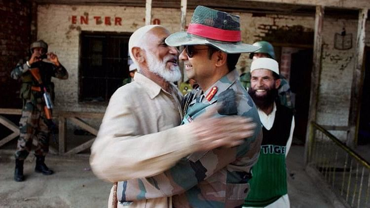 Col Dharmendra Yadav gives 'Jadoo ki Jhappi' (magical hug) to a local Imam at Rainpora in Anantnag district during the Operation 'Calm Down' of Army in South Kashmir. (Photo: PTI)