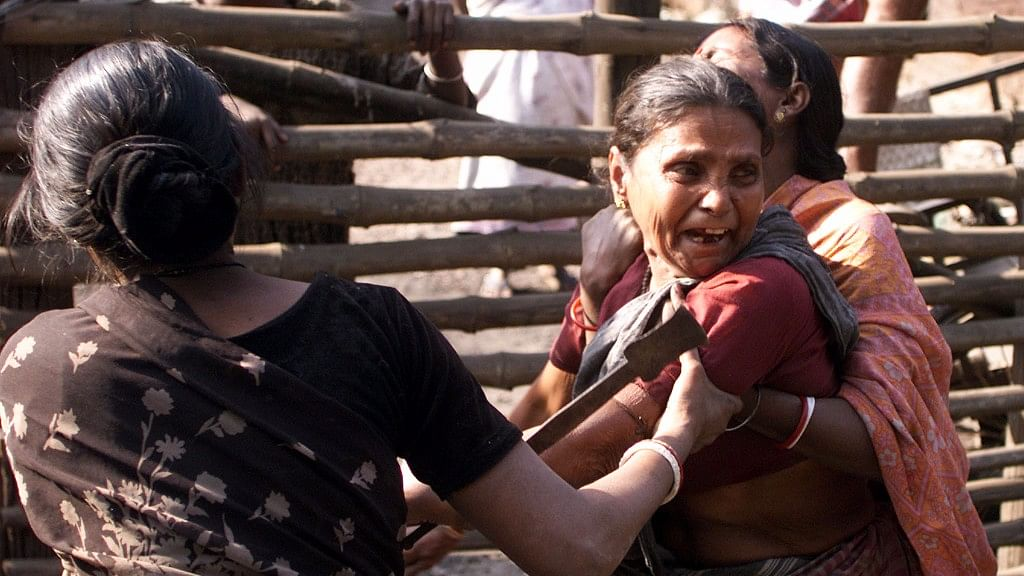 An Indian slum dweller attempts to stop a woman from trying to prevent an eviction drive by government authorities. (Photo: Reuters)