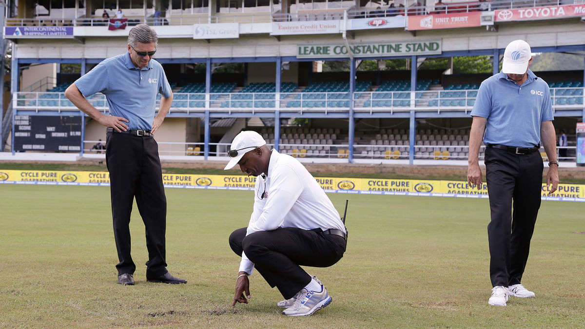 Umpires take a look at the outfield of Queen's Park Oval during India's 4th test match against West Indies. (Photo: AP)