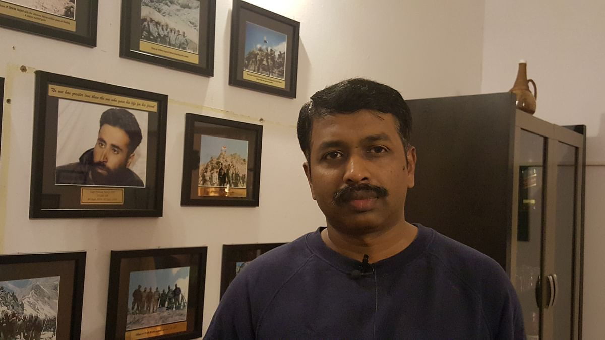 Retd Captain Naveen Nagappa at his residence where he has pictures from Operation Vijay adorning the wall. (Photo: The Quint)