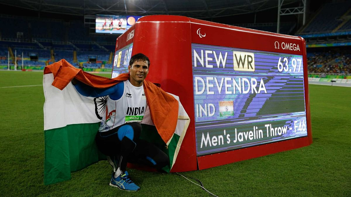 India's Devendra Jhajharia poses for the pictures next to the scoreboard that shows his world record in the men's javelin throw F46 athletics event at the Paralympic Games. (Photo: AP)
