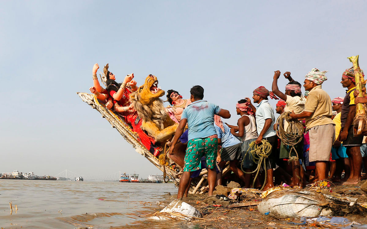 Devotees immerse an idol of Goddess Durga into the Ganga at the end of Durga Puja in Kolkata.  (Photo: Reuters/Rupak De Chowdhuri)