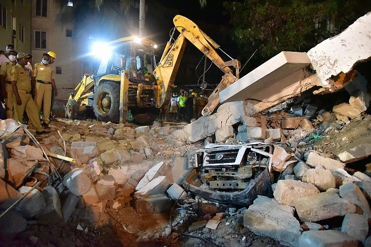 A car stuck under piles of collapsed building debris. (Photo Courtesy: <i>The News Minute</i>)