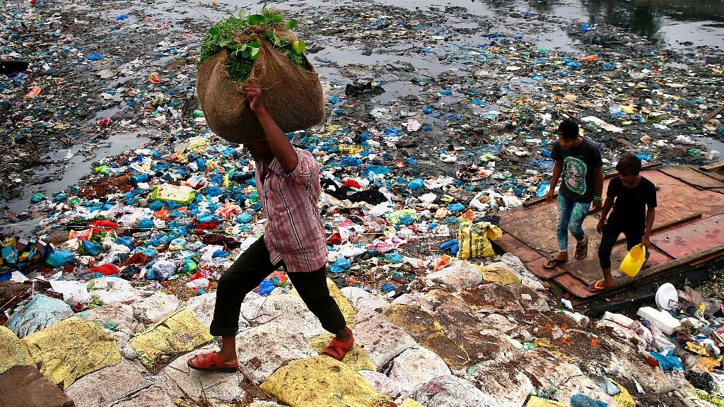 A man   walks past a polluted canal littered with plastic bags  in Mumbai, 2 October, 2016. India accounts for about 4.5 percent of global greenhouse gas emissions. (Photo:AP)