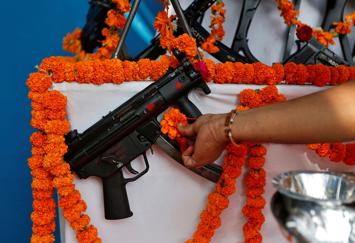 A priest offers prayers to a weapon at the police headquarters on the occasion of Dussehra in Ahmedabad. (Photo: Reuters/Amit Dave)