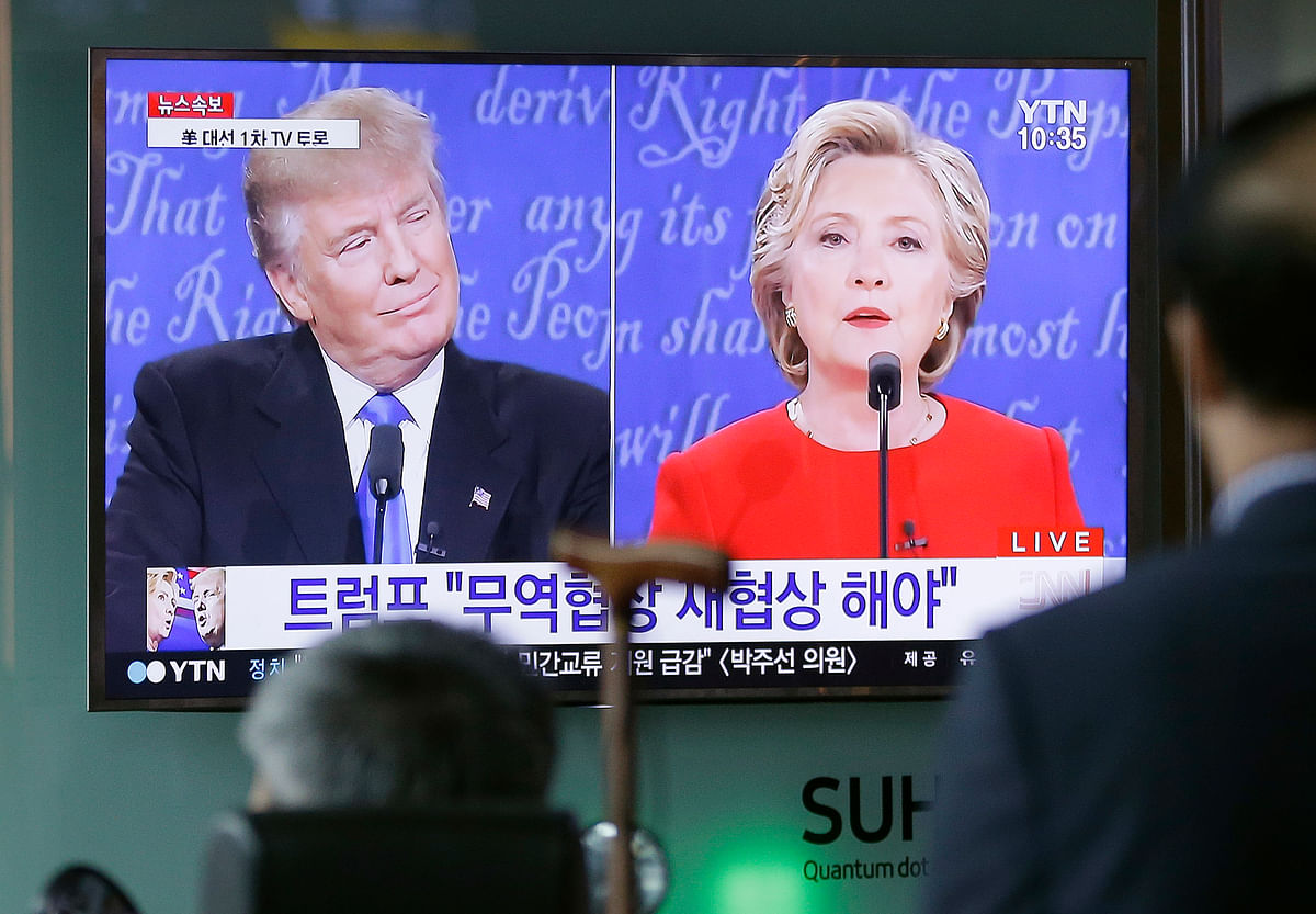 People watch a TV screen showing the live broadcast of the US presidential debate between  Hillary Clinton and Donald Trump. (Photo: AP)