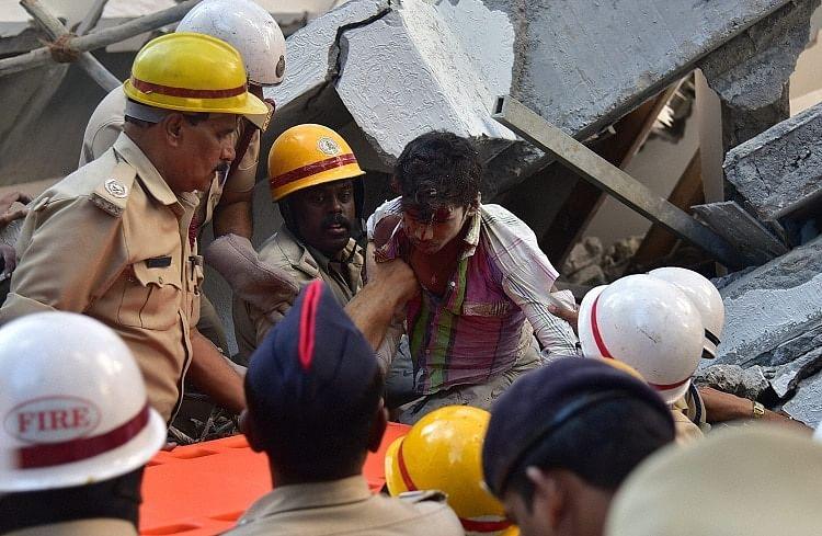 Police rescue a labourer stuck in debris. (Photo Courtesy: <i>The News Minute</i>)