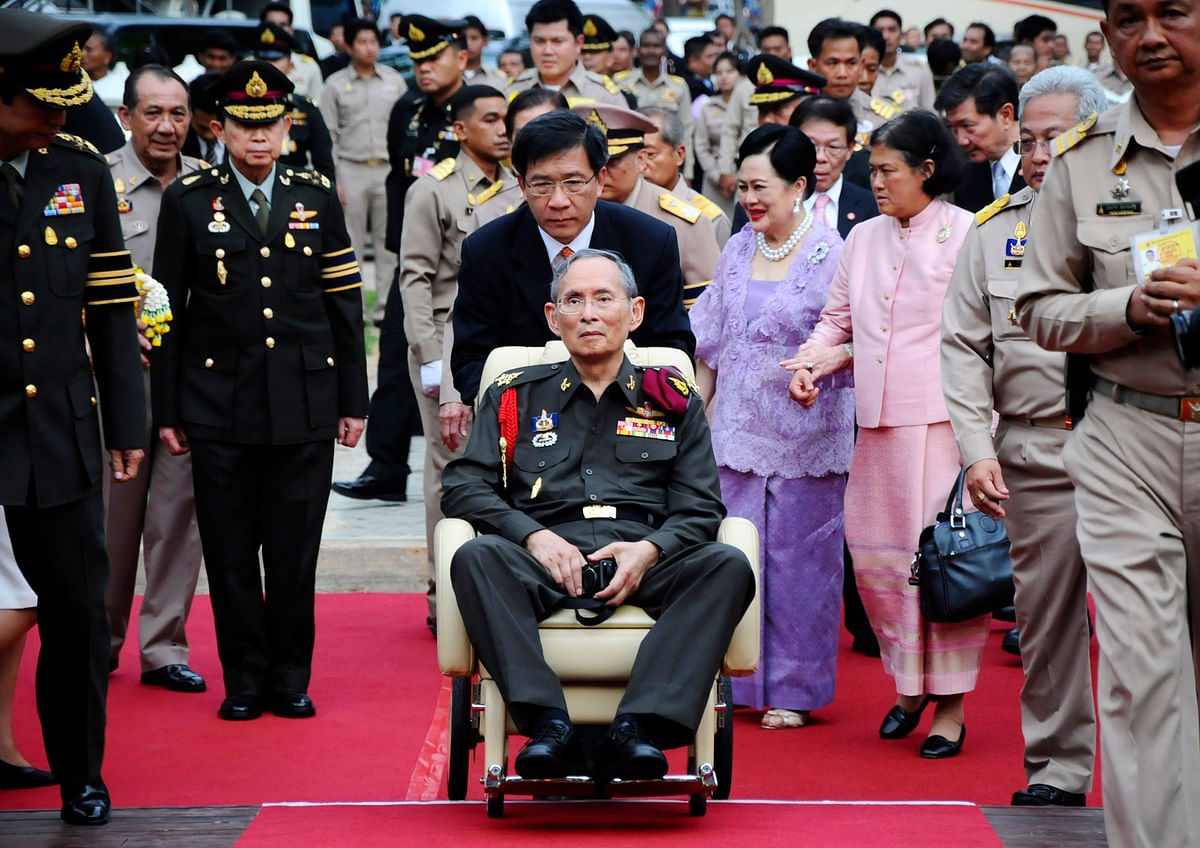 File photo of Thailand's King Bhumibol Adulyadej, center, pushed in a wheelchair as he arrives at a rice field in Ayutthaya province, 25 May 2012. (Photo: AP)