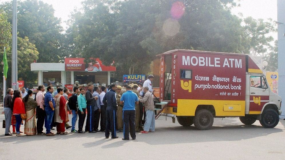 People collecting money from a mobile ATM at  Pragati Maidan in New Delhi, 14 November, 2016. (Photo: PTI)