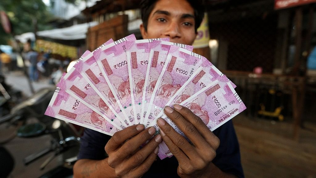File photo of an Indian man displaying new Rs 2,000 notes in Ahmadabad, India.