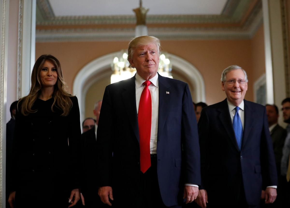 President Donald Trump and his wife Melania walk with Senate Majority Leader Mitch McConnell on Capitol Hill.