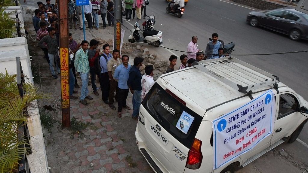 People queue up in front of a mobile ATM van in Hyderabad on 16 November, 2016. (Photo: IANS)
