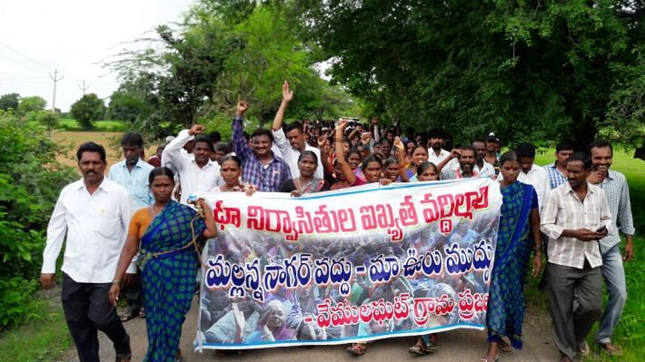 """Villagers hold a poster that says """"We don't want Mallannasagar, we want our village."""" (Photo: The News Minute)"""