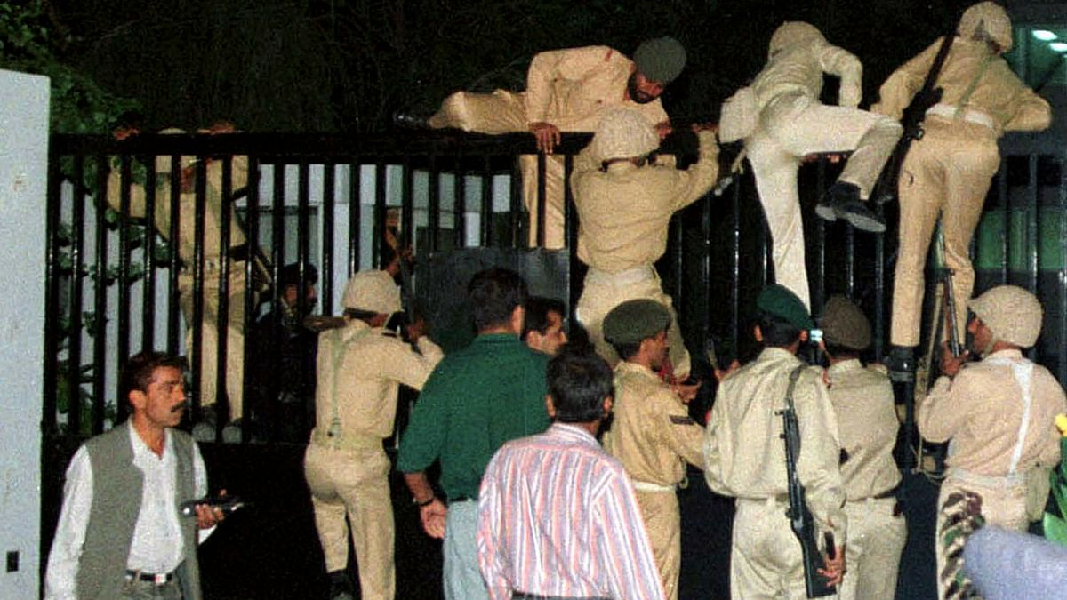 12 October 1999: Pakistan army soldiers climb over the main gate of state-run Pakistan Television (PTV) in Islamabad during General Musharraf's takeover. (Photo: Reuters)