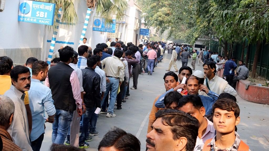 People queue up in front of an ATM  in New Delhi on  15 November, 2016. (Photo: IANS)