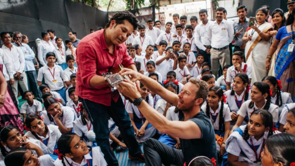 "Coldplay's Chris Martin teaches Sachin Tendulkar how to play the guitar. (Photo Courtesy: <a href=""https://twitter.com/coldplay"">Twitter/@coldplay</a>)"