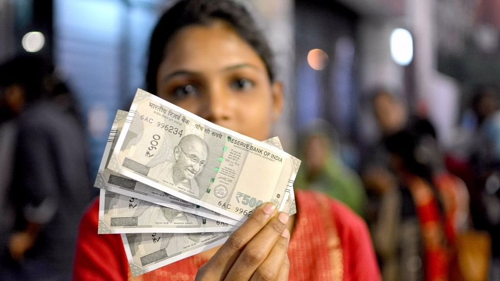 A woman holds up the new Rs 500 notes. (Photo: IANS)