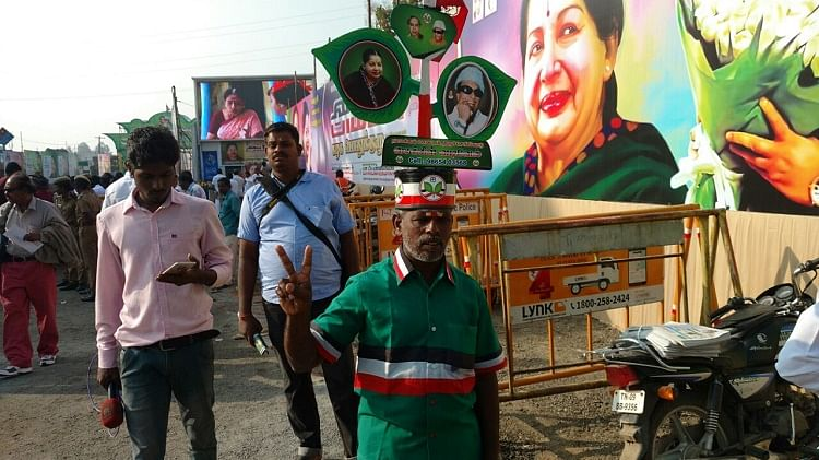 AIASMK supporter standing near a poster of J jayalalithaa in Chennai. (Photo: The News Minute)