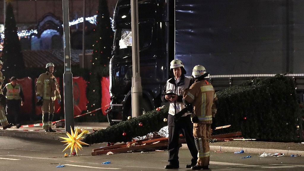 Firefighters stand beside a toppled Christmas tree after a truck ran into a crowded Christmas market and killed several people in Berlin, Germany late on Monday evening. (Photo: AP)