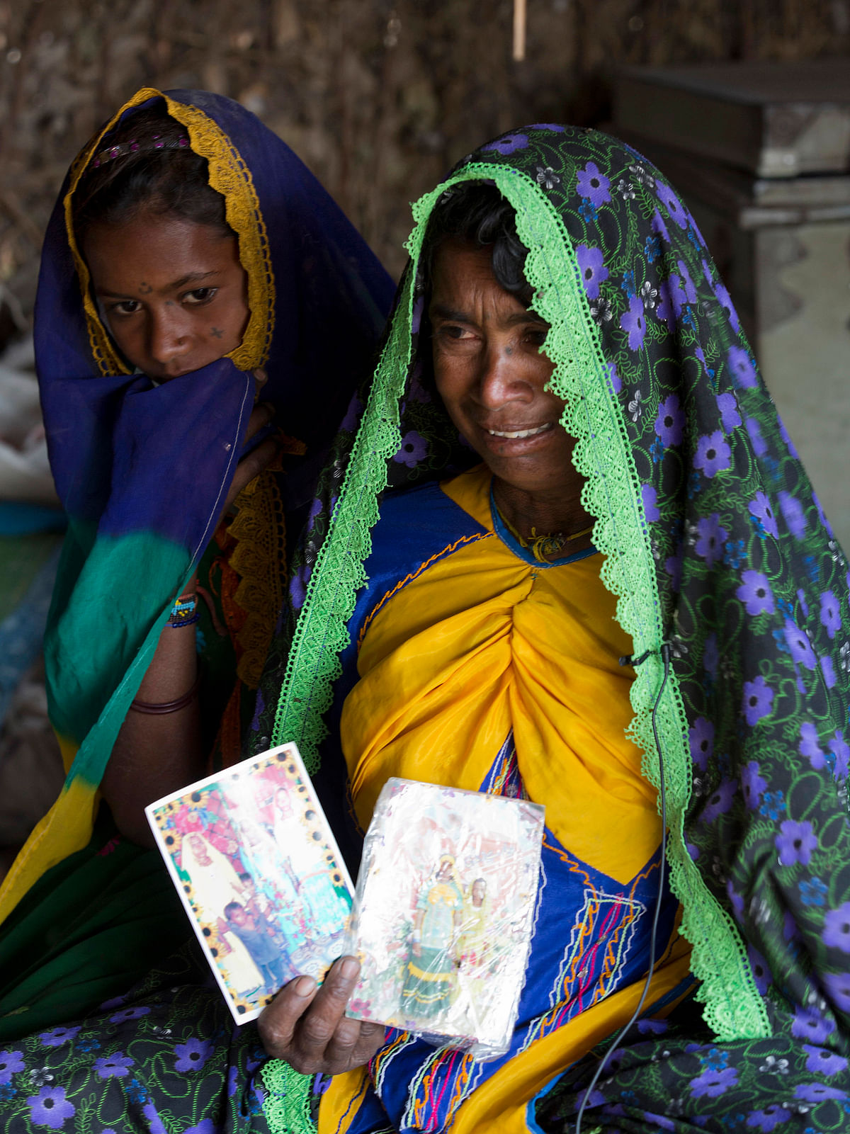Ameri Kashi Kolhi, right, in tears remembering her daughter while holding her pictures of Jeevti, with her younger daughter Saveeta in Mir Pur Khas, Pakistan. (Photo: AP)