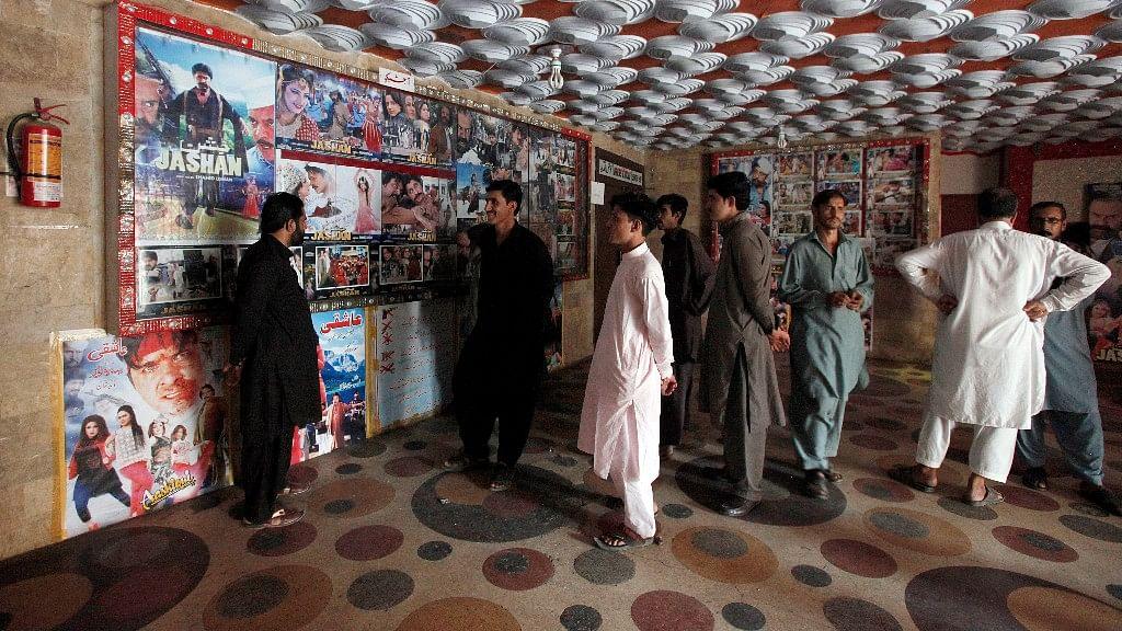 Pakistani cinema-goers look at photos displayed at a local cinema in Karachi, Pakistan, Sunday, 18 December 2016.  (Photo: AP)