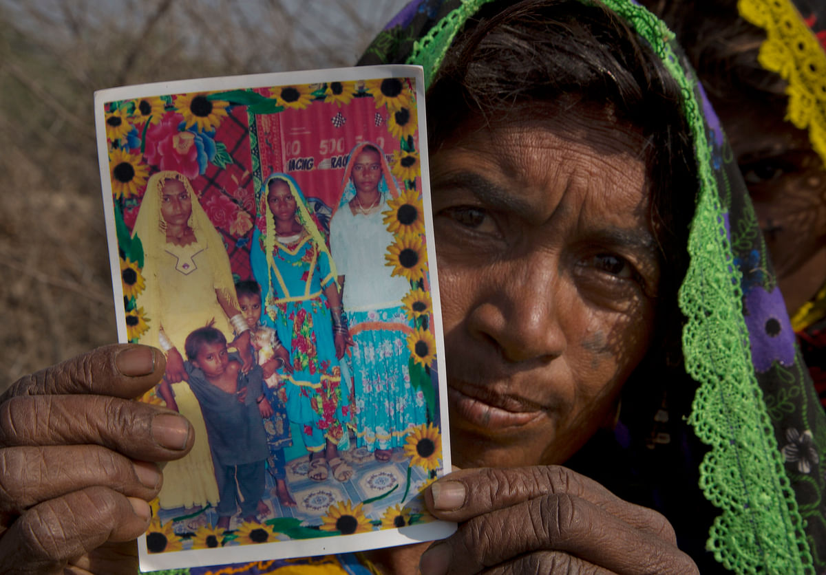 Ameri Kashi Kolhi shows picture of her daughter Jeevti, right, in Payro Lundh, Pakistan.(Photo: AP)
