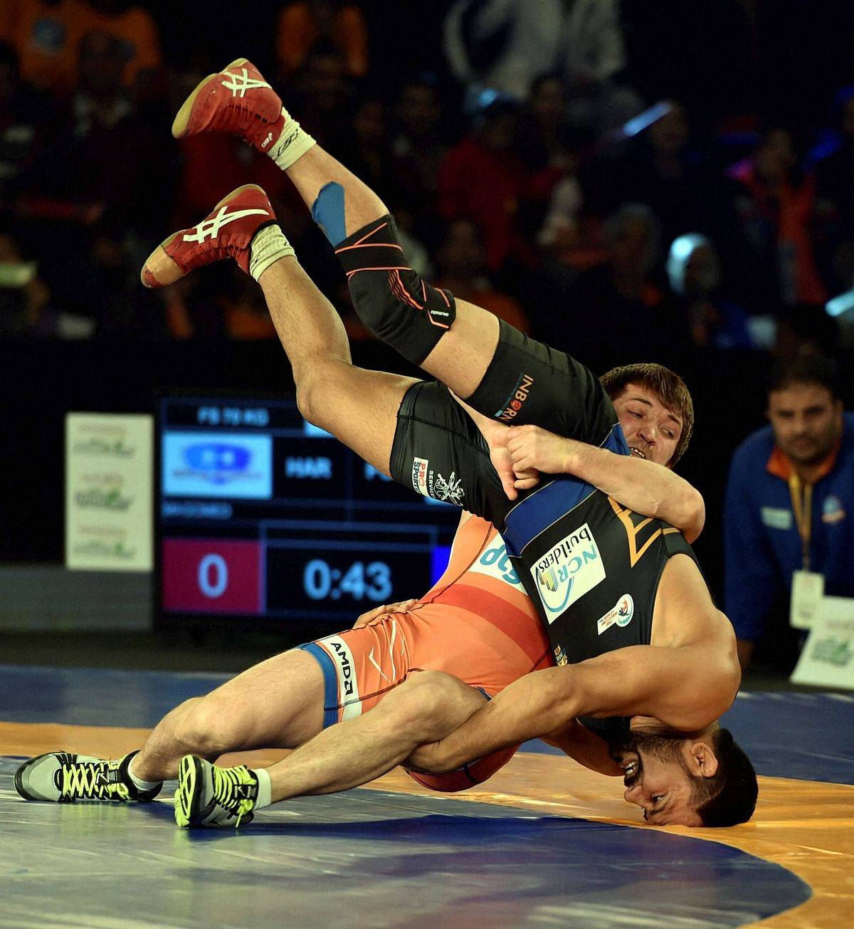 Haryana Hammers' Vladimir Khinchegashvili (red) competes against Sandeep Tomar of Punjab Royals in the men's 57 kg category. (Photo: PTI)