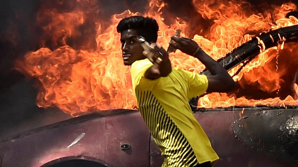 A pro-Jallikattu protester throwing bottles at police personnel during a clash near Marina Beach in Chennai, 23 January 2017.