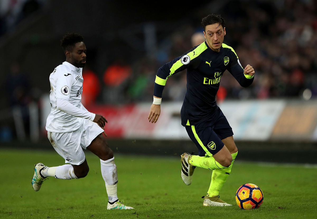 Arsenal's Mesut Ozil, right, Swansea City's Nathan Dyer battle for the ball. (Photo: AP)