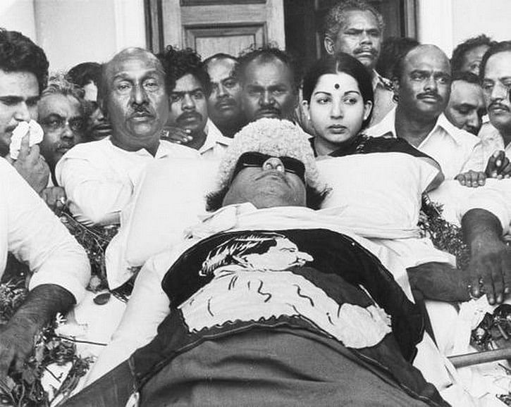"""MGR's body lies in state at Rajaji Hall in Chennai. Jayalalithaa can be seen standing beside his body. (Photo: <a href=""""http://MGR's body lies in state at Rajaji Hall in Chennai. Jayalalithaa can be seen standing beside his body. (Photo: kmhouseindia Blogspot)"""">kmhouseindia blogspot</a>)"""