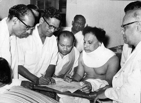 """MGR, wearing a neck cast, is seen in his hospital bed signing his nomination papers for the St Thomas Mount constituency. (Photo Courtesy: <a href=""""http://peopleofindia1868-1875photos.blogspot.in/2011/09/posted-by-beyondet.html"""">Blogspot</a>)"""