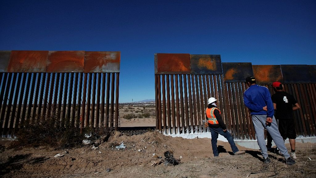 A worker chats with residents at a newly built section of the US-Mexico border fence at Sunland Park.