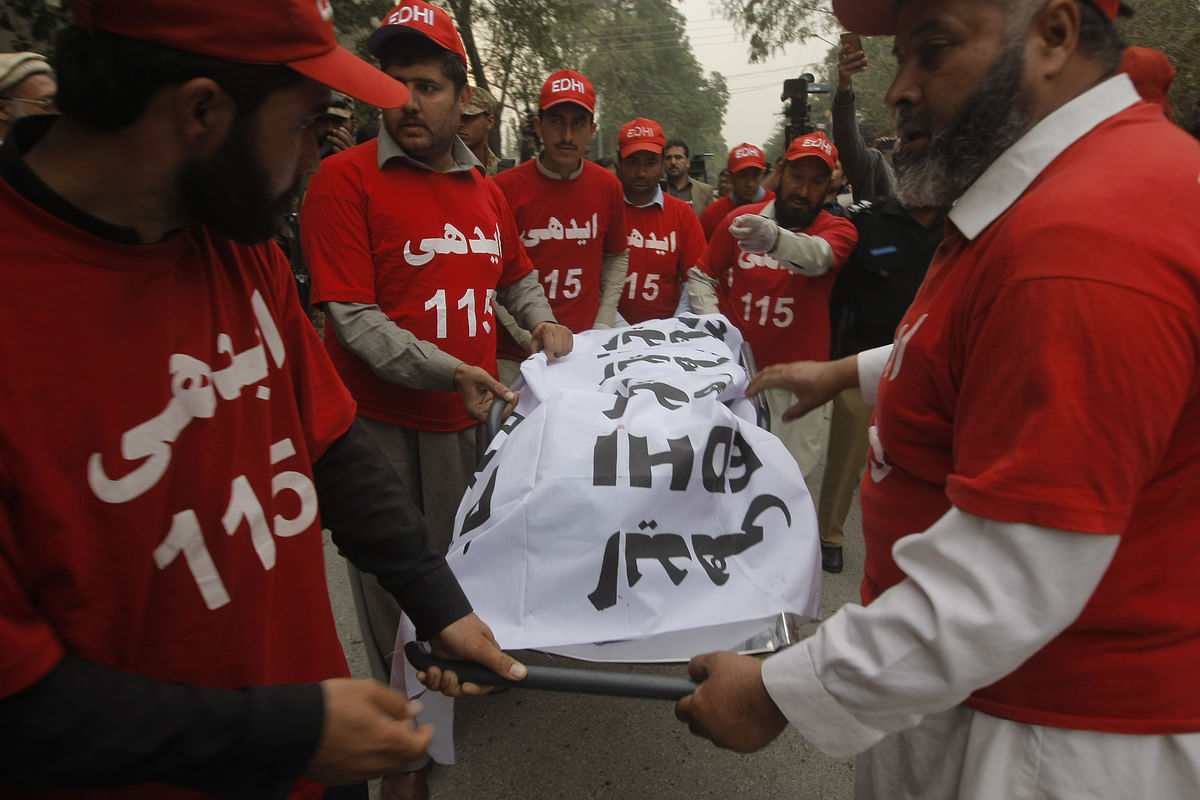 Pakistani volunteers remove a body from the site of a bombing in Peshawar in Pakistan. (Photo: AP)