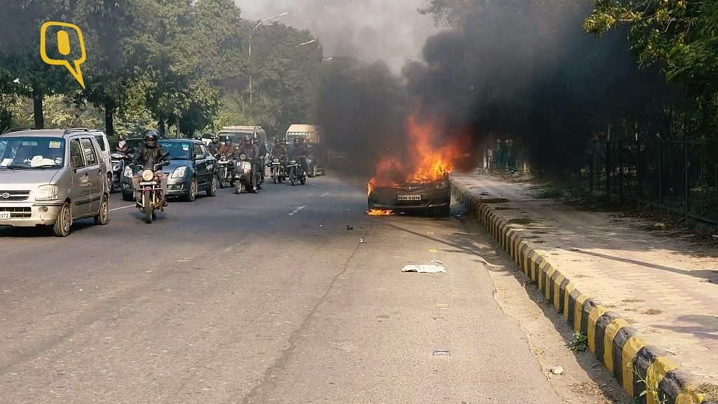 A car caught fire on the busy Dadri Main Road near Noida Sector 15A. (Photo: <b>The Quint</b>)