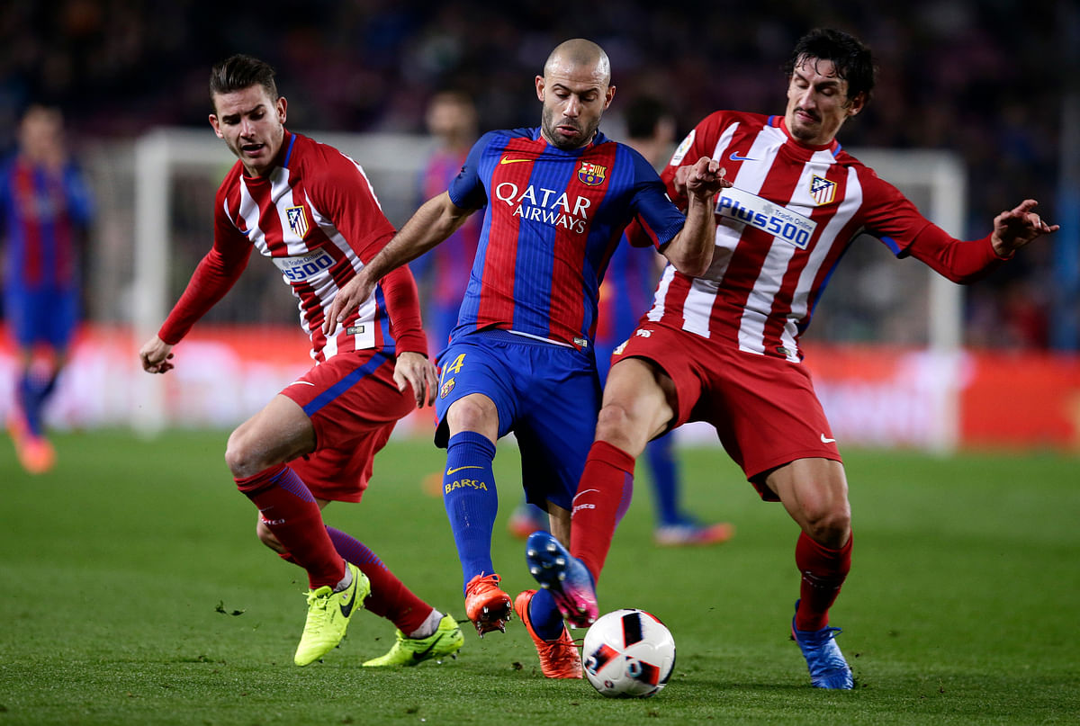 Barcelona's Javier Mascherano, center, fights for the ball with Atletico's Lucas Hernandez and Stefan Savic. (Photo: AP)